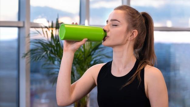 Młoda blondynka w odzieży sportowej pije wodę podczas treningu z zamkniętymi oczami