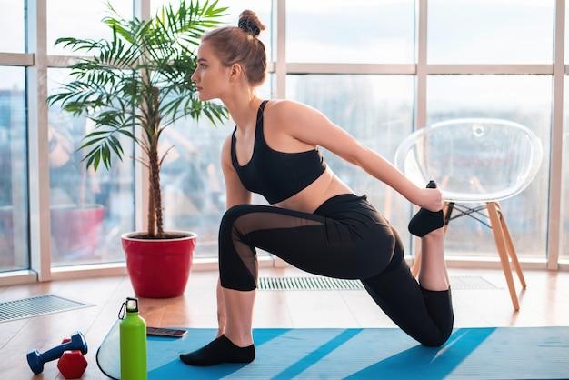 Młoda blondynka w odzieży sportowej robi joga na macie