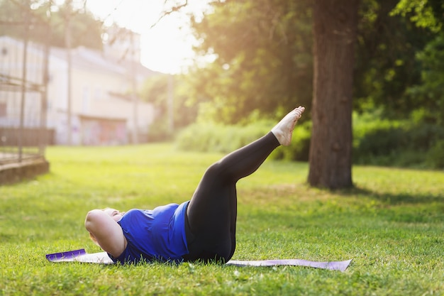 Młoda blondynka w rozmiarze plus wykonuje w parku ćwiczenia na mięśnie brzucha