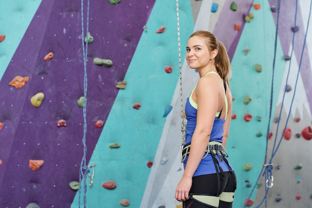 Młoda blondynka w specjalnej odzieży wspinaczkowej stoi przy ścianie z wielokolorowymi skałami i patrzy na ciebie