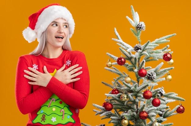 Młoda blondynka w świątecznym swetrze i czapce mikołaja, patrząc na bok, trzymając się za ręce na klatce piersiowej radosna i pozytywna pozycja obok choinki na pomarańczowym tle