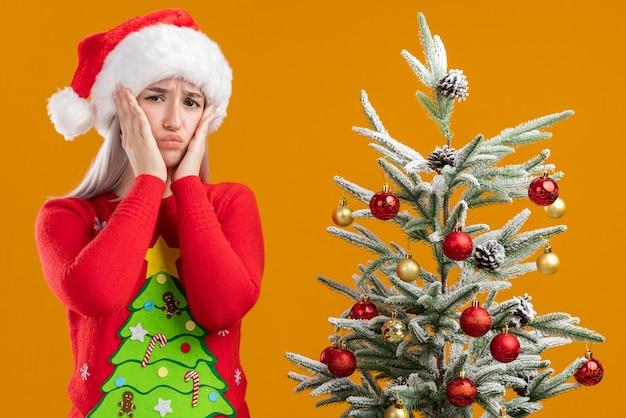 Młoda blondynka w świątecznym swetrze i czapce mikołaja patrząc na kamerę zdezorientowana i bardzo niespokojna stoi obok choinki na pomarańczowym tle