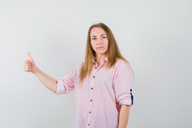 Młoda blondynka w swobodnej różowej koszuli pokazującej kciuk w górę