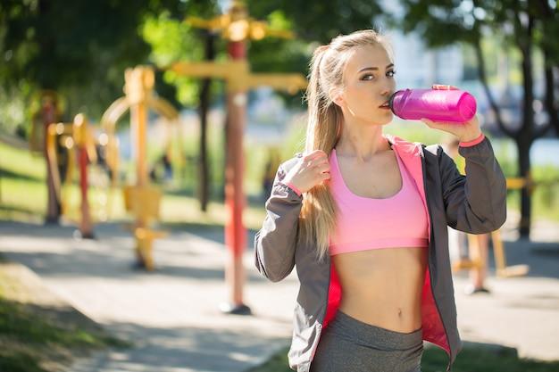 Młoda blondynka wody pitnej podczas porannego joggingu