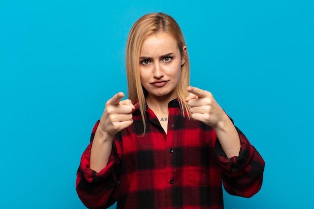 Młoda blondynka wskazująca na aparat z obu palców i zły wyraz, mówiąc ci, abyś wypełnił swój obowiązek