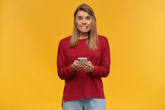 Młoda blondynka wygląda na niepewną siebie, jakby miała kłopoty lub niezręczną sytuację, trzyma telefon w dłoniach, patrzy na aparat ze strachem, lekko przygryza wargę