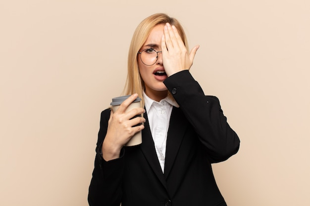 Młoda blondynka wygląda na zaspaną, znudzoną i ziewającą, z bólem głowy i jedną ręką zakrywającą połowę twarzy
