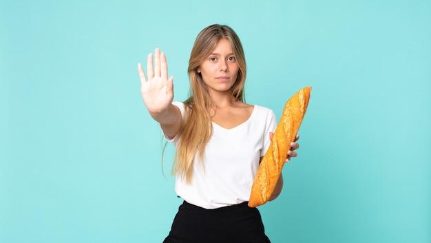 Młoda blondynka wygląda poważnie pokazując otwartą dłoń, robiąc gest zatrzymania i trzymając bagietkę z chlebem