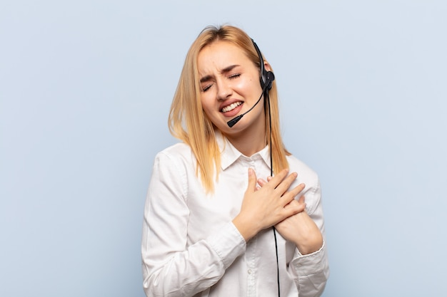 Młoda blondynka wyglądająca na smutną, zranioną i załamaną, trzymająca obie ręce blisko serca, płacząca i przygnębiona