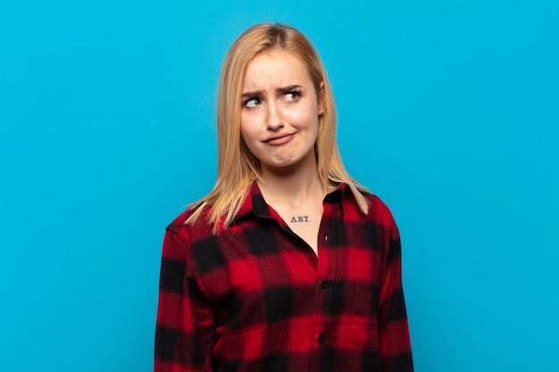 Młoda blondynka wyglądająca na zaskoczoną i zdezorientowaną, zastanawiająca się lub próbująca rozwiązać problem lub myśląca