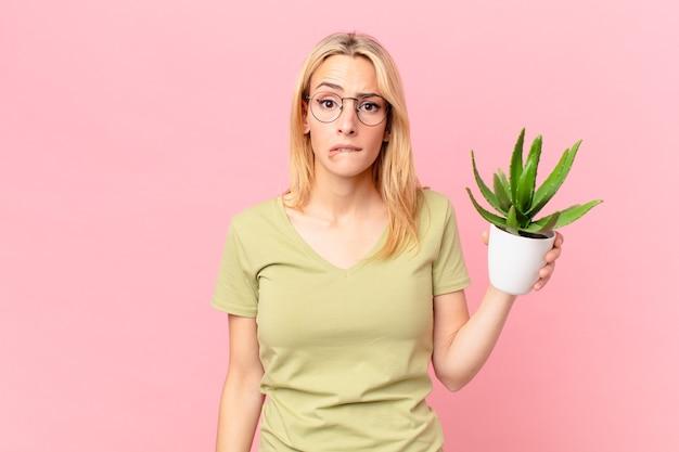Młoda blondynka wyglądająca na zdziwioną i zdezorientowaną, trzymająca kaktusa