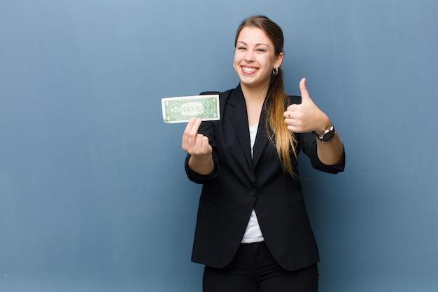 Młoda blondynka z banknotów dolara przed grunge ścianą