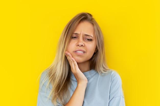 Młoda blondynka z bólem zęba trzymająca się za policzek na żółtym tle