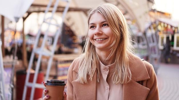 Młoda blondynka z filiżanką kawy kobieta w food court