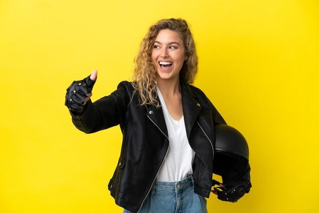 Młoda blondynka z kaskiem motocyklowym na białym tle na żółtym tle dająca gest kciuka w górę