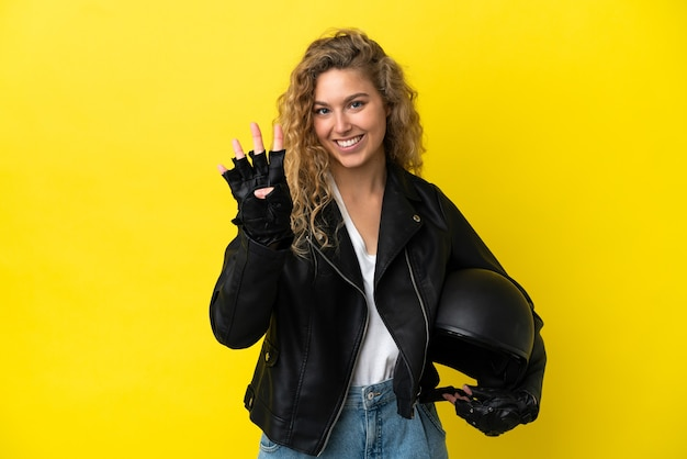 Młoda blondynka z kaskiem motocyklowym na białym tle na żółtym tle szczęśliwa i licząca cztery palcami