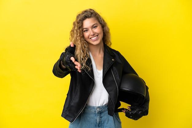 Młoda blondynka z kaskiem motocyklowym na żółtym tle, ściskając ręce, aby zamknąć dobrą ofertę