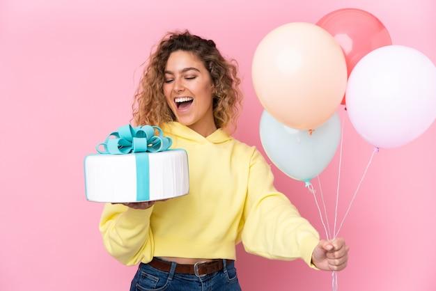 Młoda blondynka z kręconymi włosami, łapiąca wiele balonów i trzymająca duży tort na różowej ścianie