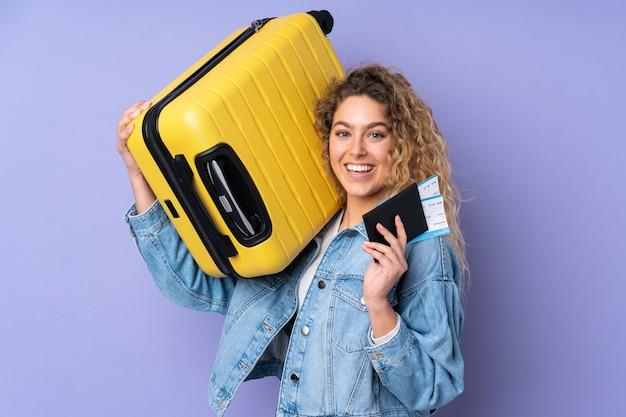 Młoda blondynka z kręconymi włosami na białym tle na fioletowej ścianie w wakacje z walizką i paszportem i zaskoczona
