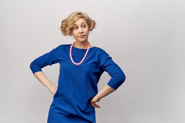 Młoda blondynka z krótkimi włosami i lokami, pozuje do zdjęć w studio. ma na sobie niebieską sukienkę i klasyczne koraliki. przyjazny wyraz twarzy i spojrzenie w bok. ręce spoczywały na jej biodrach.