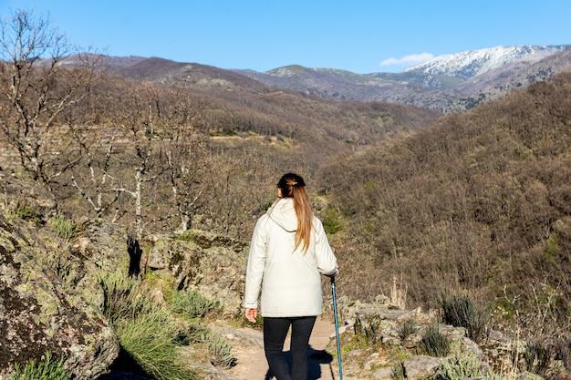 Młoda blondynka z kucykiem wędrówki w naturalnym krajobrazie z kijem trekkingowym.