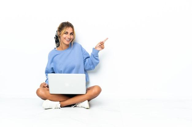 Młoda blondynka z laptopa na białym tle palcem wskazującym na bok
