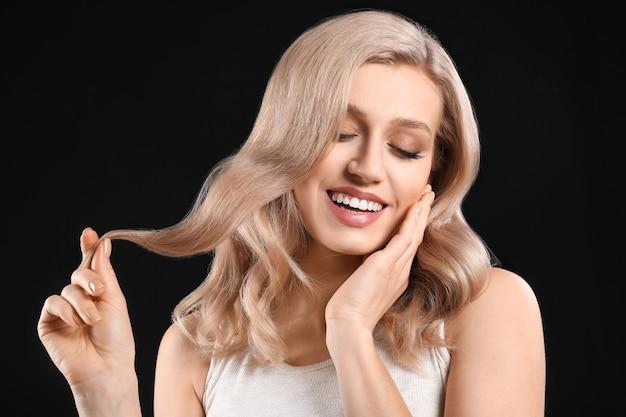 Młoda blondynka z pięknymi włosami na ciemnym tle