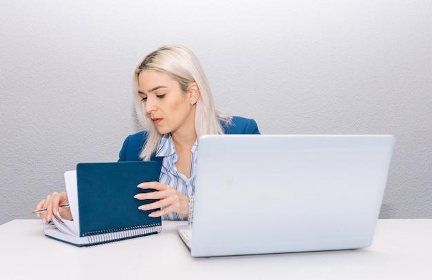 Młoda blondynka z platynowymi włosami, ubrana w niebieską marynarkę, telepracuje z domu z laptopem i pisze w swoim porządku obrad. koncepcja telepracy.