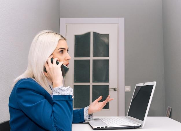 Młoda blondynka z platynowymi włosami ubrana w niebieski blezer telepracy z domu z telefonem i laptopem. koncepcja telepracy. widok z boku