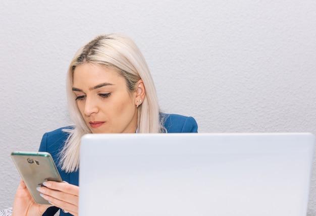 Młoda blondynka z platynowymi włosami ubrana w niebieski blezer telepracy z domu z telefonem i laptopem. koncepcja telepracy.