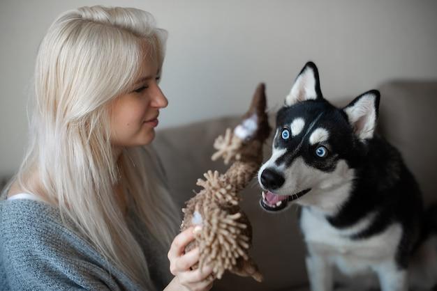 Młoda blondynka z psem husky syberyjskim na kanapie