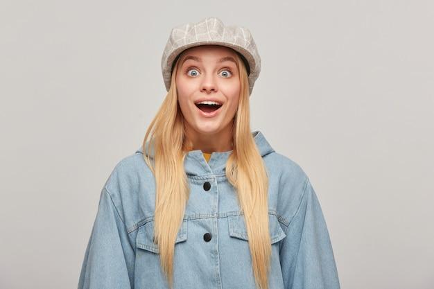 Młoda blondynka z rozpuszczonymi włosami, raduje się, czuje wielką radość i zachwyt, wyłupiasta, nosi oversizową dżinsową kurtkę, beżową kraciastą czapkę, na szarym tle