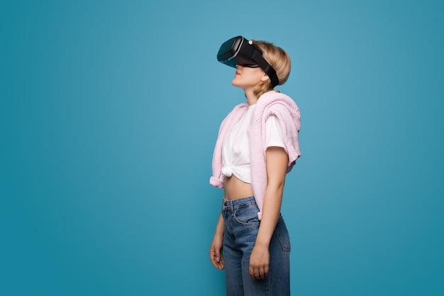Młoda blondynka za pomocą zestawu słuchawkowego wirtualnej rzeczywistości i pozowanie na niebieskiej ścianie