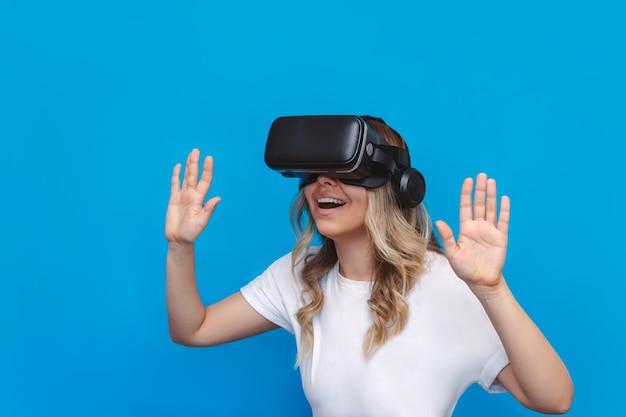 Młoda blondynka zachwycona zdumiona kobieta w białej koszulce patrzy w czarne okulary wirtualnej rzeczywistości na niebieskiej ścianie