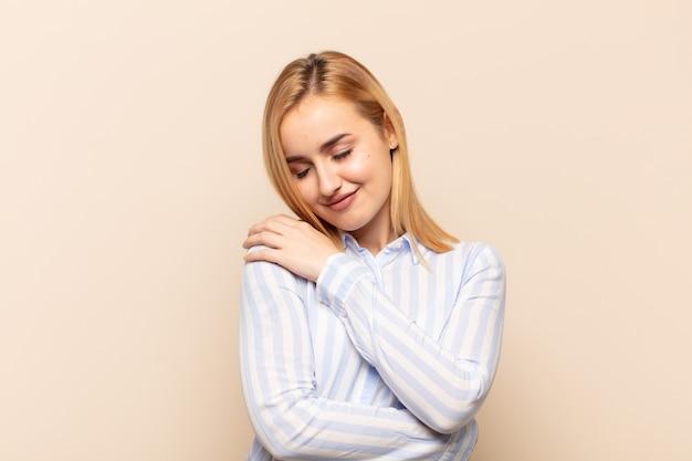 Młoda blondynka zakochana, uśmiechnięta, przytulająca się i przytulająca, pozostająca samotna, samolubna i egocentryczna