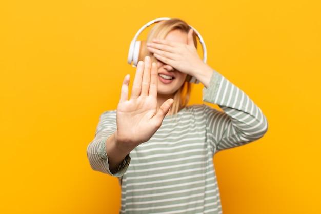 Młoda blondynka zakrywa twarz ręką i kładzie drugą rękę do góry, aby zatrzymać aparat, odmawiając zdjęć lub zdjęć