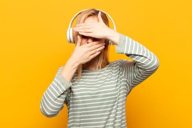 Młoda blondynka zakrywająca twarz obiema rękami, mówiąc nie do aparatu! odmawianie zdjęć lub zakaz zdjęć