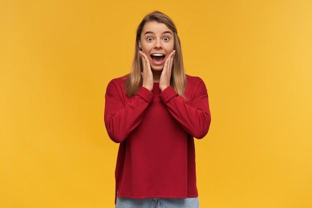 Młoda blondynka zaskoczona i zszokowana wspaniałą wiadomością, trzyma dłonie przy policzkach