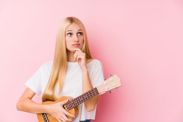 Młoda blondynki dziewczyna bawić się ukelele patrzeje z ukosa z wątpliwym i sceptycznym wyrażeniem.