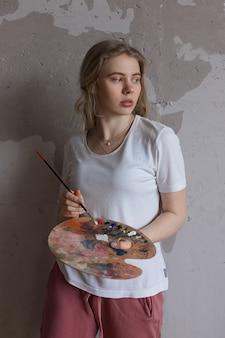 Młoda blondynki dziewczyna miesza kolory na palecie z muśnięciem