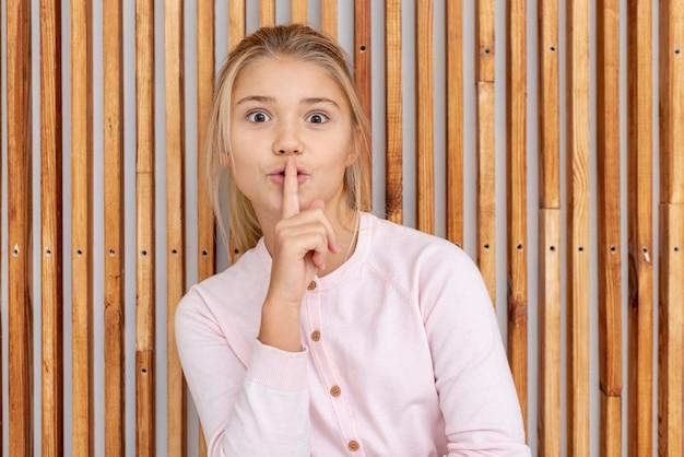 Młoda blondynki dziewczyna robi cii znakowi