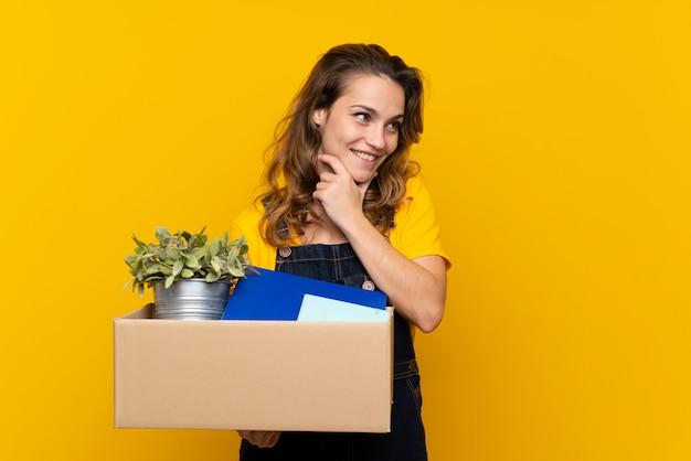 Młoda blondynki dziewczyna robi ruchowi podczas gdy podnoszący pudełko pełno rzeczy patrzeje stronę