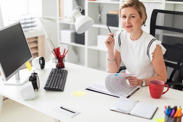 Młoda blondynki dziewczyna siedzi przy komputerowym biurkiem w biurze, trzyma ołówek w jej ręce