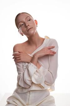 Młoda blondynki dziewczyna w biały stroju pozować