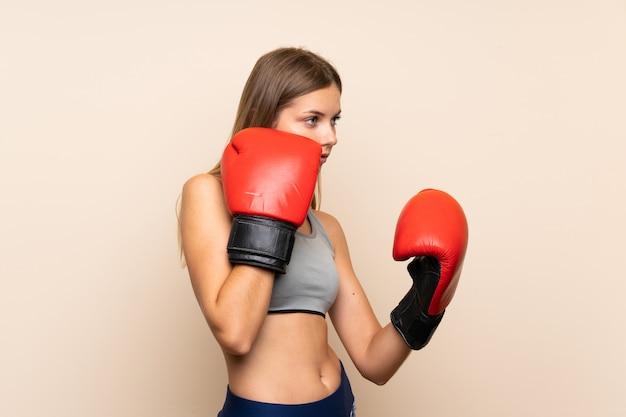 Młoda blondynki dziewczyna z bokserskimi rękawiczkami nad odosobnionym tłem