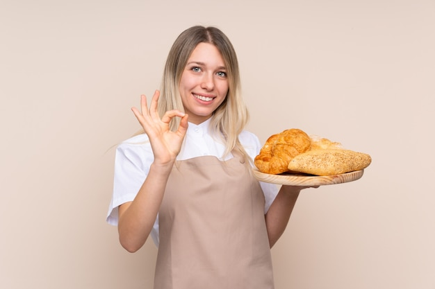 Młoda blondynki dziewczyna z fartuchem. żeński piekarz trzyma stół z kilka chlebami pokazuje ok znaka z palcami