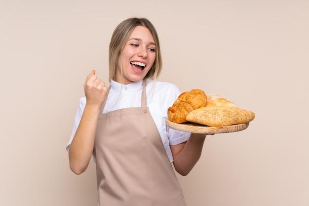 Młoda blondynki dziewczyna z fartuchem. żeński piekarz trzyma stół z kilka chlebami świętuje zwycięstwo