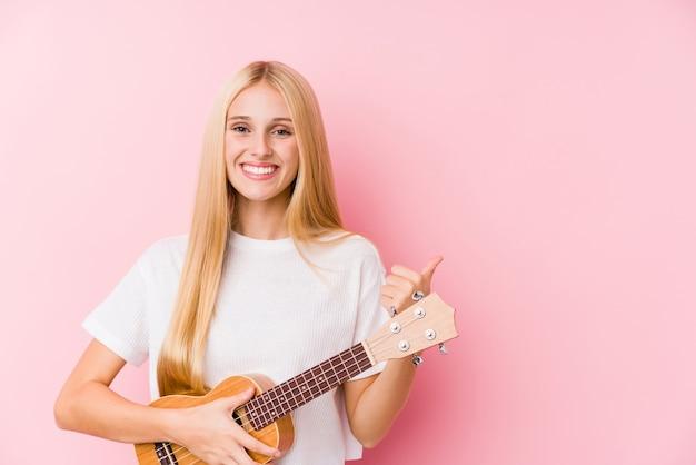 Młoda blondynki kobieta bawić się ukelele uśmiecha się kciuk up i podnosi