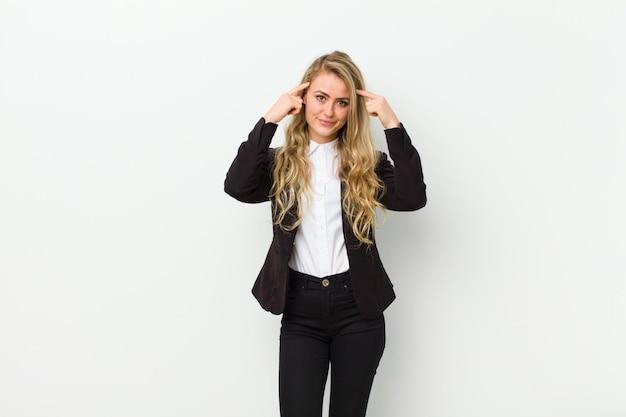 Młoda blondynki kobieta czuje się zmieszana lub wątpiąca, koncentruje się na pomysle, mocno myśli, chce skopiować przestrzeń na boku na białej ścianie