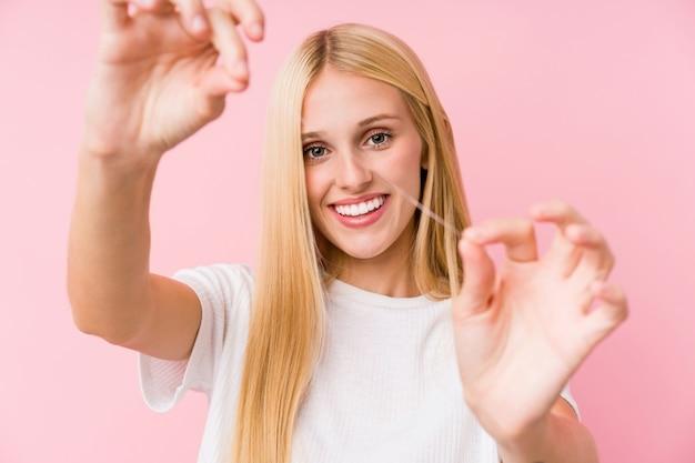 Młoda blondynki kobieta czyści jej zęby z nicią dentystyczną
